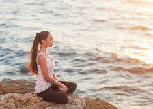 Girl in lotus pose at sunset. Young refined girl, sits in a lotus position on a rock by the sea in the rays of the setting sun Stock Photos