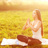 Girl in lotus pose at sunset Royalty Free Stock Image