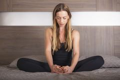 Girl in lotus position practicing yoga royalty free stock photography