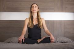 Girl in lotus position practicing yoga royalty free stock images