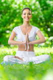Girl in lotus position prayer gesturing Royalty Free Stock Photo