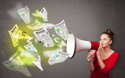 Girl into loudspeaker and newspapers fly out Royalty Free Stock Image