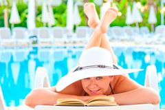 Girl in a lounge chair near the pool with his legs crossed smiling Royalty Free Stock Image
