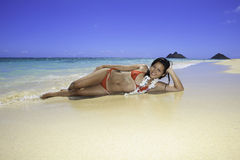 Girl lounging on the sand Stock Images