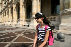 Girl at the Louvre. Tourist girl with headphone in Paris royalty free stock photos