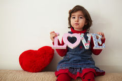 Girl with love sign and red plush heart Stock Photos