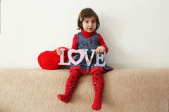 Girl with love sign and red plush heart Royalty Free Stock Photo