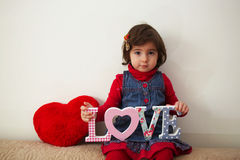 Girl with love sign and red plush heart Royalty Free Stock Images