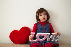Girl with love sign and red plush heart Stock Images