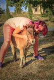 Woman with farm pony. Young and smiling woman hugging a Shetland pony in the countryside Royalty Free Stock Image