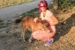Woman with a pony. Young and smiling  woman with a Shetland pony in the countryside Stock Image