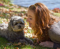 Girl loves shih-poo dog. Girl lays in the grass and leaves with her pet shih-poo dog on fall day royalty free stock images