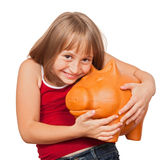 Girl loving her piggy bank Stock Photography