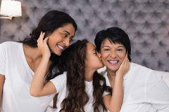 Girl loving mother and grandmother in bedroom Royalty Free Stock Photos