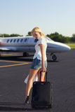 The girl with luggage going to plane Royalty Free Stock Photography