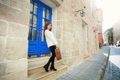 Girl with luggage left her house on the street of the old town Stock Images