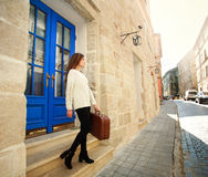 Girl with luggage left her house on the street of the old town Stock Photo