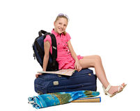 Girl with luggage and map sitting on a suitcase Stock Image