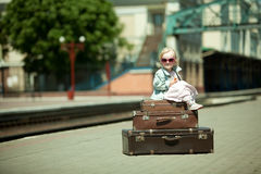 Girl with luggage at the railway station Stock Images