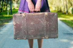 Girl with luggage on the road. Girl with old suitcase on the road royalty free stock images