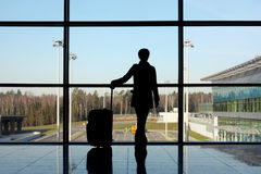 Girl with luggage standing in airport Royalty Free Stock Photos
