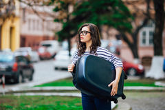 Girl with luggage walking city street Stock Photography