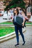 Girl with luggage walking  street Stock Photo
