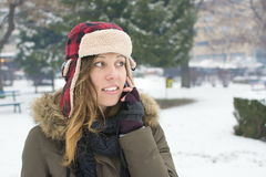 Girl with a lumberjack hat talking on her cellphone. In the snow Stock Photos