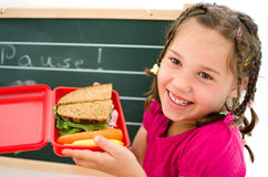 Girl with Lunbox. Laughing girl opens a healthy lunchbox in front of a blackboard Royalty Free Stock Photo