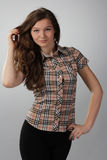 Girl with lush hair in a checkered shirt on Stock Images