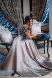 Girl in a luxurious, evening dress. Sits on a chair Royalty Free Stock Image