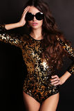 Girl with luxurious long dark hair wearing sequin corset and sunglasses Stock Photos