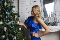 Girl in luxurous blue dress near christmas tree Royalty Free Stock Photos