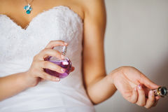 Girl in Luxury White Wedding Dress Spraying Perfume. Girl in luxury white wedding dress spraying from perfume bottle on wrist. Bride holds perfume in hand and Royalty Free Stock Images