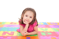 Girl lying on alphabet mat. Girl lying on colorful mat resting head on hands. Isolated on white Royalty Free Stock Photo