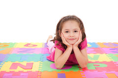 Girl lying on alphabet mat. Girl lying on colorful mat resting head on hands. Isolated on white Stock Photography