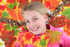 Girl lying between autumn leaves Stock Images