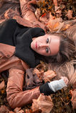 Girl lying on the autumn leaves Royalty Free Stock Image
