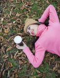Girl lying on autumn leaves with coffee Stock Photos