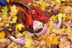 Girl lying in autumn leaves portrait. Royalty Free Stock Photos