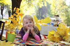 Girl lying with autumn leaves under trees Stock Photography