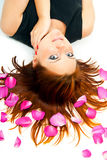 Girl lying on a background of rose petals Stock Photo