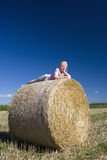Girl (11-13) lying on bale of hay, low angle view royalty free stock photos