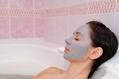 The girl is lying in the bathroom with a mask on her face Royalty Free Stock Images