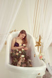 Girl lying in the bathroom with roses Stock Images