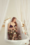 Girl lying in the bathroom with roses Royalty Free Stock Photos