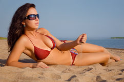 Girl lying on the beach. Girl with black sunglasses lying on the beach. Strewing sand through palm stock images