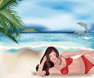 Girl lying on beach and dolphins Royalty Free Stock Photography