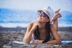 Girl is lying on the beach with hat and swimsuit Royalty Free Stock Images