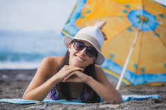 Girl is lying on the beach with hat and swimsuit Royalty Free Stock Photos